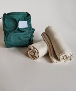 Vikblöjor, prova på-paket. Ett PUL-skal i grönt med två ihoprullade vikblöjor bredvid.